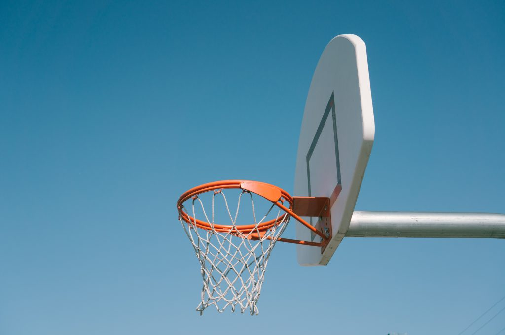 basketball hoop backboard net against bright blue sky