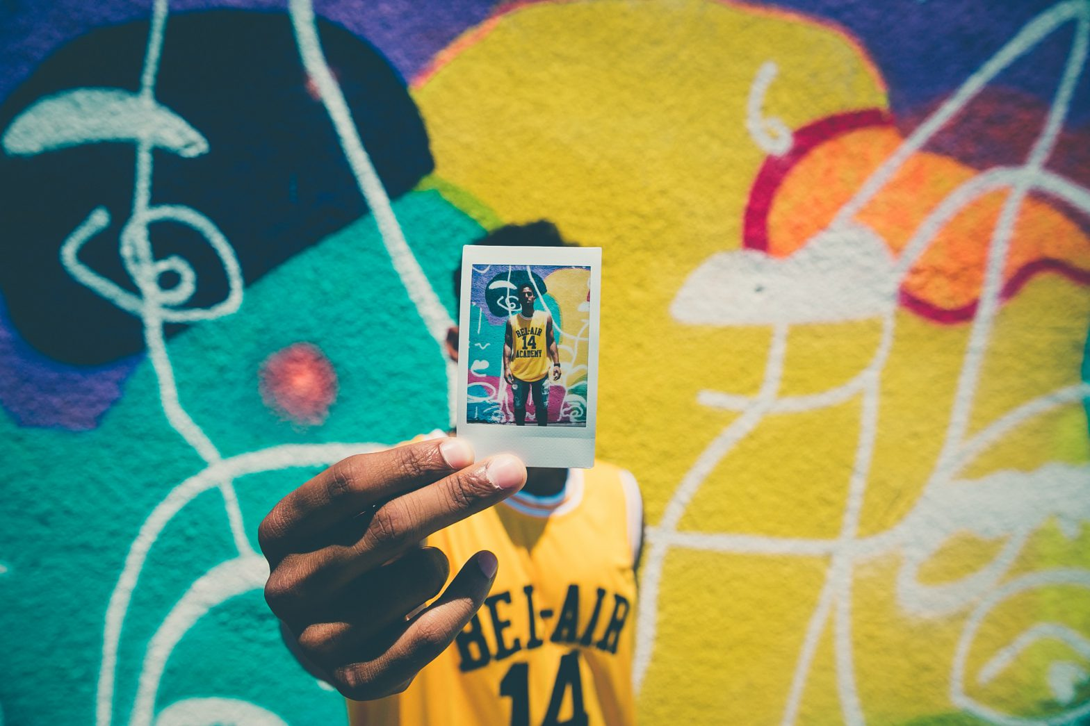 basketball player holding polaroid of self mural in background