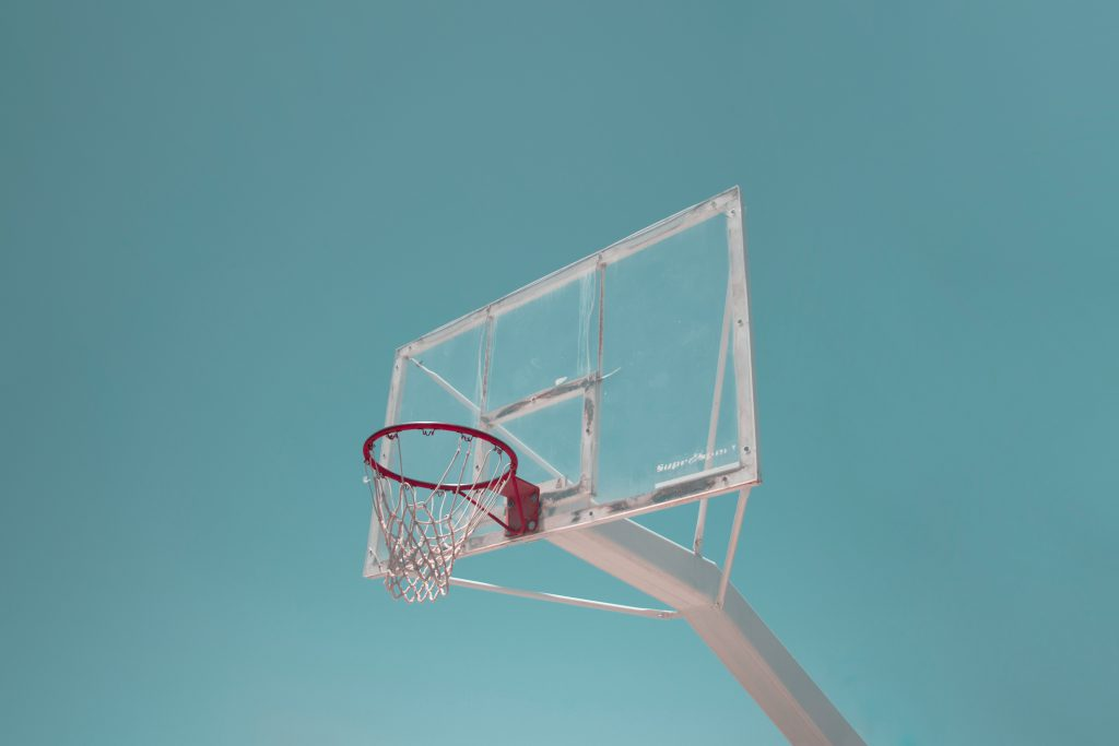 basketball hoop net glass backboard against turquoise blue sky retro filter