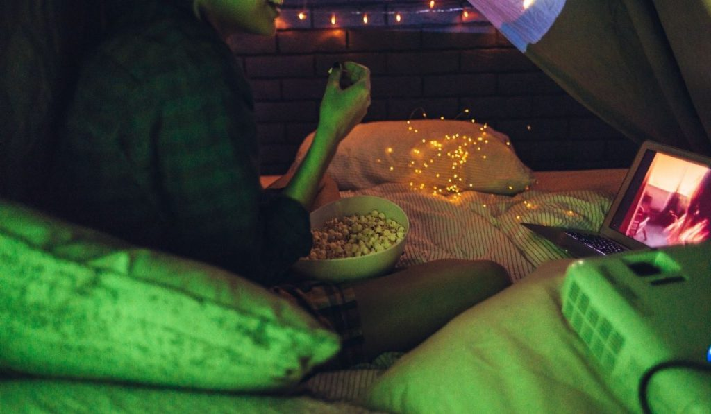 a girl with a bowl of popcorn watching a movie