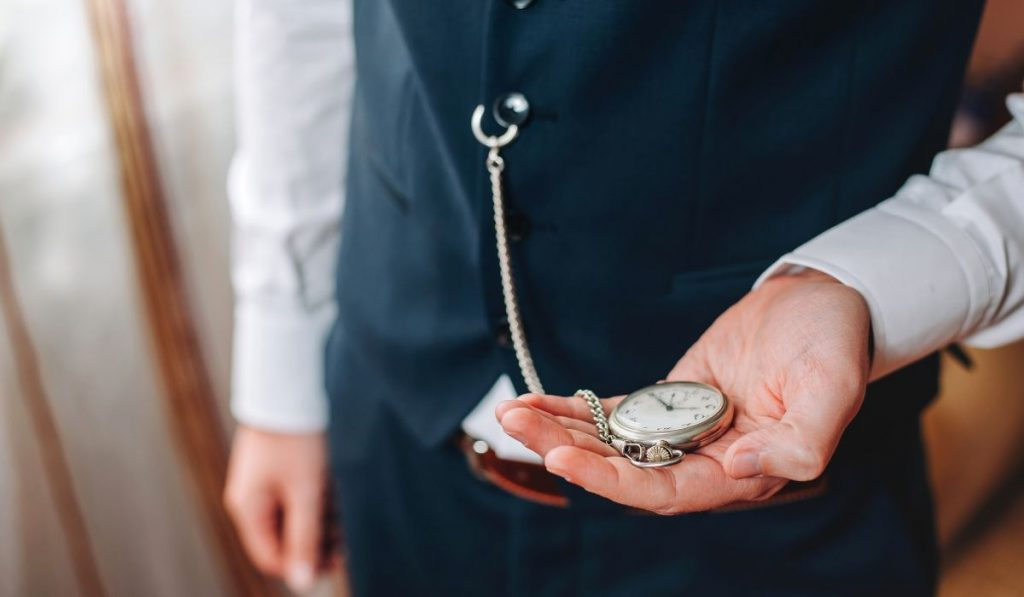 a man holiding a pocket watch.
