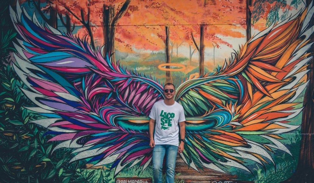 a boy posing behind a mural artwork of an angel's wing