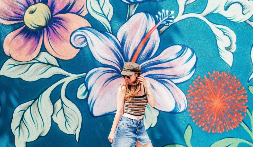 a girl posing behind a mural artwork of different flowers