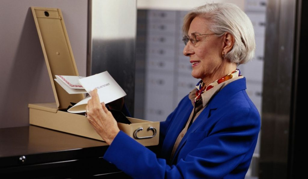 a lady holding important documents stored in a safe deposit box